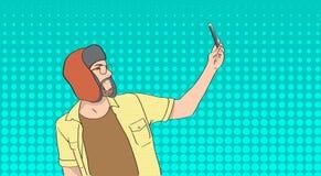 男服拍在聪明的电话流行艺术五颜六色的减速火箭的样式的冬天帽子Selfie照片 库存照片