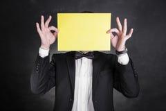 男服黑无尾礼服拿着在面孔前面的纸 库存照片