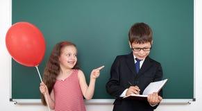 男生和女孩孩子有气球的在获得黑板的背景乐趣 库存照片
