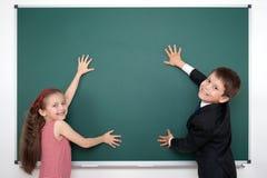 男生和女孩被投入的手在空白的黑板和做框架,教育概念 库存照片