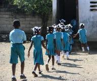 男生和女孩赶紧回到类在Robillard,海地 免版税库存图片