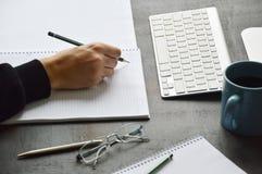 男生在有计算机的书桌上学习 免版税图库摄影