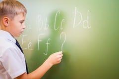 男生在黑板写与白垩的英语字母表 免版税库存照片