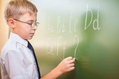 男生在黑板写与白垩的英语字母表 库存照片