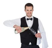 男管家倾吐的香槟画象到玻璃里 免版税库存图片