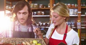 男职工拿着菜的篮子和有剪贴板的女职工