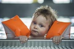 男婴做在游泳池的面孔 库存照片
