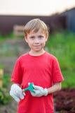 男婴儿童开掘测试花花盆从事园艺的绿色植物塑料作用铁锹小孩 免版税库存照片