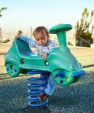 男婴儿童游戏在操场区域 免版税库存图片