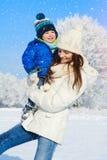 男婴和母亲画象在冬日-雪落 免版税图库摄影