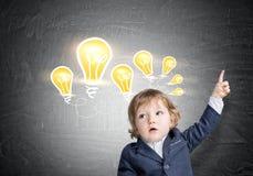 男婴和电灯泡在黑板 库存照片