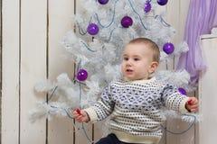 男婴在圣诞节杉树下 库存照片