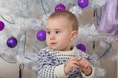 男婴在圣诞节杉树下 免版税库存照片
