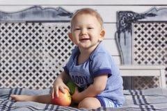 男婴在父母的床上用石蜡苹果 免版税库存图片