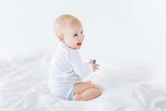 男婴坐在白色隔绝的床, 1岁婴孩概念 库存照片