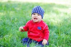 男婴坐草户外 免版税库存照片