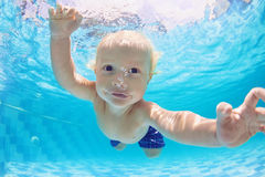 男婴游泳和潜水画象水下在水池 免版税库存照片