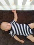 男婴睡着在小儿床 免版税库存照片