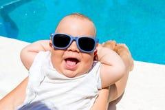 男婴获得与他的母亲的乐趣在蓝色水池 免版税库存图片