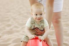 男婴获得在海滩的乐趣 图库摄影