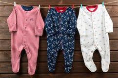 男婴衣裳& x28; sleepsuits& x29;垂悬在晒衣绳 免版税库存照片