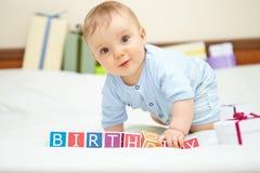 男婴画象在床上的。生日概念。 免版税库存图片