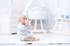 男婴饮用奶在晴朗的托儿所 库存照片