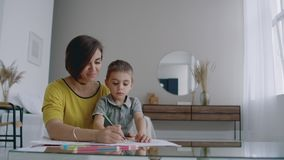 画一起做的年轻女人和孩子与铅笔的图片在舱内甲板 股票录像