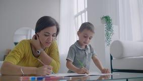 画一起做的年轻女人和孩子与铅笔的图片在舱内甲板 影视素材