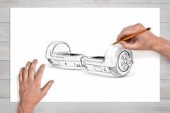 画与一支铅笔的男性手一gyroscooter在一张大纸 库存图片