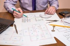画与与测量仪器和膝上型计算机的建筑学的手 免版税库存照片