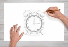 画与两响铃的男性手一个减速火箭的警报块使用在白皮书的一支铅笔在接近的看法 库存图片