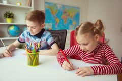 画与五颜六色的铅笔的两个逗人喜爱的孩子 免版税库存照片
