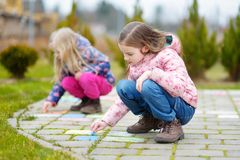 画与在边路的五颜六色的白垩的两个愉快的孩子 小孩子的夏天活动 图库摄影