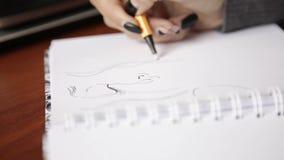 画与铅笔的女性手一张面孔在笔记本 影视素材