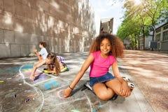 画与chalck比赛微笑的女孩跳房子 免版税图库摄影
