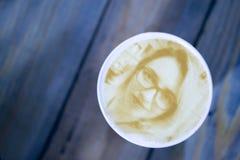 画在泡沫咖啡拿铁的妇女的面孔在3D打印机创造的玻璃 免版税图库摄影