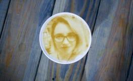 画在泡沫咖啡拿铁的妇女的面孔在3D打印机创造的玻璃 库存照片