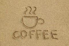 画在湿沙子的一份杯子和题字咖啡 库存照片