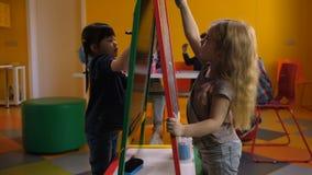 画在画架板的逗人喜爱的不同的女孩在类 股票视频