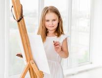 画在画架的一个小女孩的画象一张图片 免版税库存照片