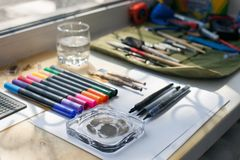 画家、图表设计师或者书法工作区,另外种类工具,刷子,标志和笔,安置准备好现在创造d 库存照片