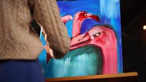 画家完成画桃红色火鸟的图象,做条纹白色染料 股票视频