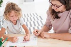 画房子的小孩使用有femal的他的五颜六色的蜡笔 免版税库存照片