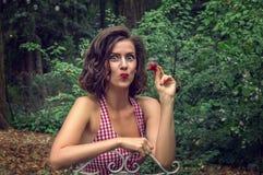 画报女孩吃红色草莓 在面孔有情感地被显示的欢欣和乐趣 免版税图库摄影