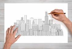 画有许多摩天大楼的男性手一个城市绉纱有在白皮书的一支铅笔的在接近的看法 免版税图库摄影