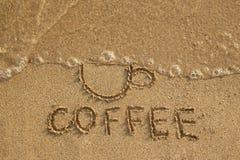 画杯子由在湿沙子的波浪和题字咖啡,顶视图冲走了 概念健康生活方式 免版税库存图片