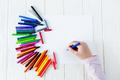 画的学校用品在桌上:纸和蜡笔 孩子在他的手上拿着一只蜡笔 免版税图库摄影