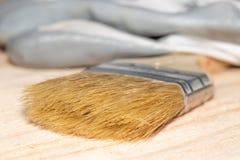 画笔和手套在木桌上 免版税图库摄影