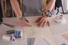 画衣裳的女性时装设计师剪影在工作室 免版税库存图片